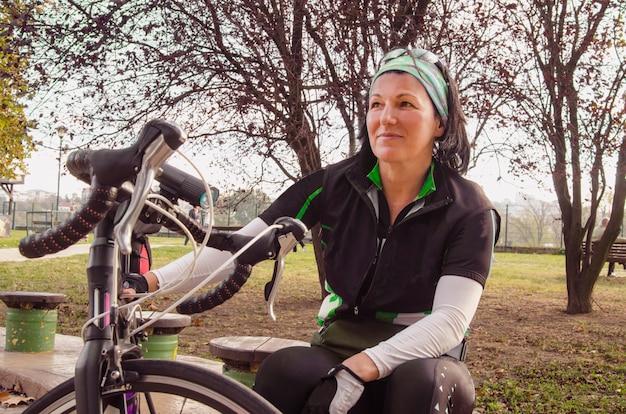 Mulher jovem ciclista descansando no parque. menina sentado e relaxando para viagem de passeio de bicicleta