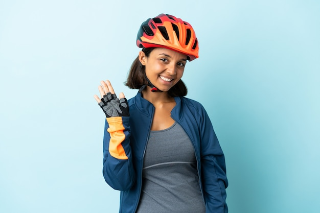 Mulher jovem ciclista isolada em azul saudando com a mão com expressão feliz