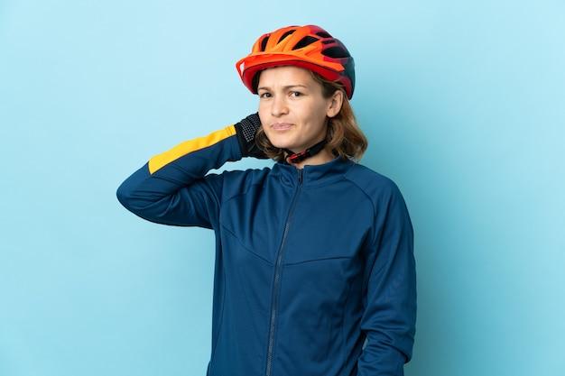 Mulher jovem ciclista isolada em fundo azul com dúvidas