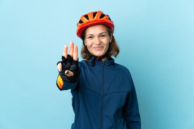 Mulher jovem ciclista isolada em um fundo azul feliz e contando três com os dedos