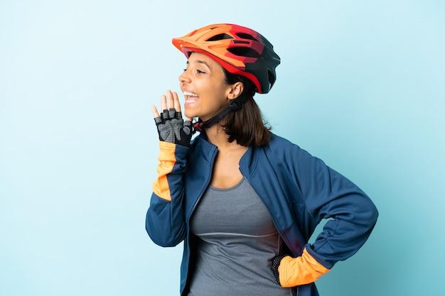 Mulher jovem ciclista isolada em um fundo azul gritando com a boca bem aberta para o lado