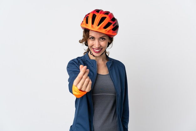 Mulher jovem ciclista isolada na parede branca fazendo gesto de dinheiro