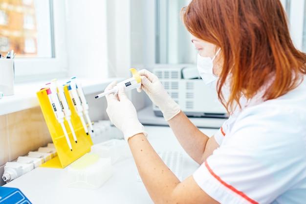 Mulher jovem cientista em um jaleco branco e máscara trabalha no laboratório médico ou biológico moderno, preparando-se para o teste de dna