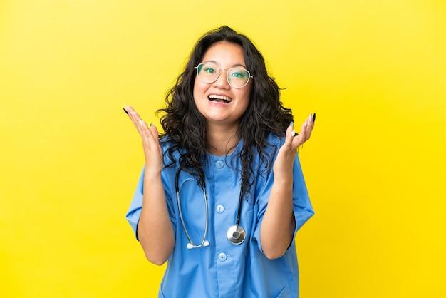 Mulher jovem cirurgiã asiática isolada em um fundo amarelo com expressão facial surpresa
