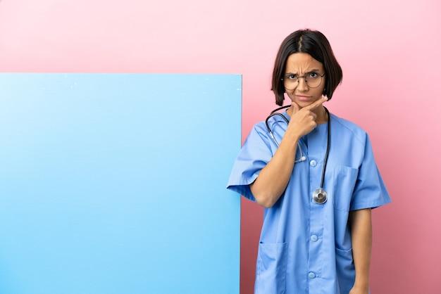 Mulher jovem cirurgiã de raça mista com um grande banner isolado fundo tendo dúvidas