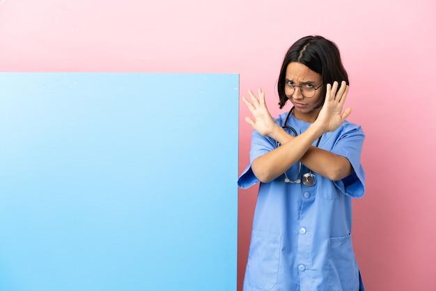 Mulher jovem cirurgiã de raça mista com um grande banner sobre fundo isolado nervosa esticando as mãos para a frente