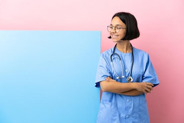 Mulher jovem cirurgiã de raça mista com um grande banner sobre um fundo isolado com os braços cruzados e feliz