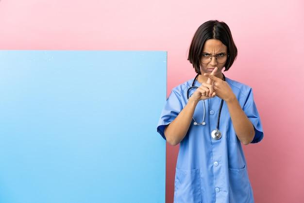Mulher jovem cirurgiã de raça mista com um grande banner sobre um fundo isolado, fazendo um gesto de parada com a mão para interromper um ato