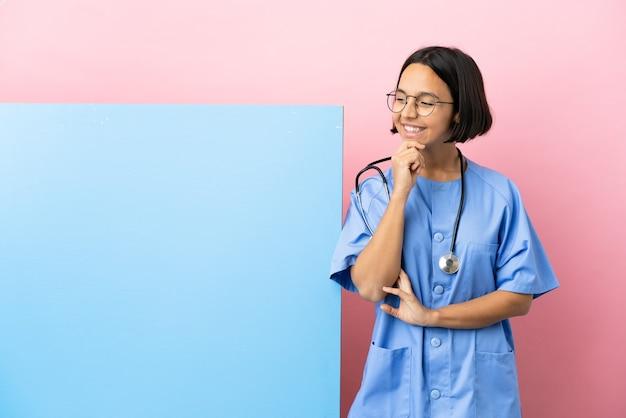 Mulher jovem cirurgiã de raça mista com um grande banner sobre um fundo isolado, olhando para o lado e sorrindo