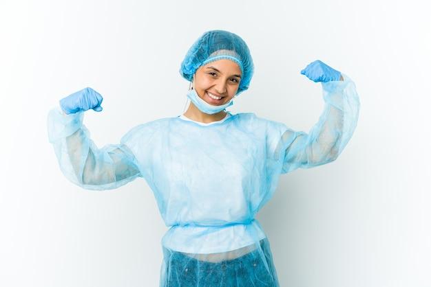 Mulher jovem cirurgiã latina isolada em fundo branco mostrando gesto de força com os braços, símbolo do poder feminino