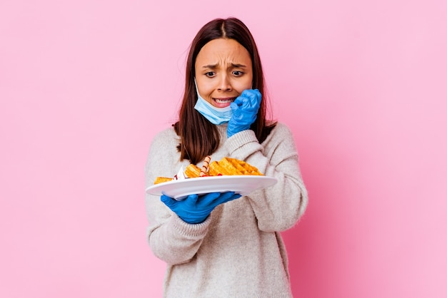 Mulher jovem cirurgiã segurando um waffle isolado
