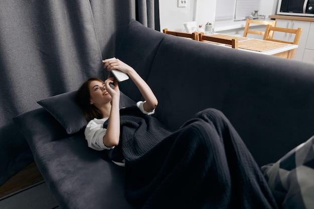 Mulher jovem coberta com um cobertor deitada no sofá com um telefone celular na mão, vista de cima