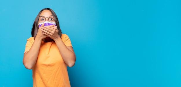 Mulher jovem cobrindo a boca com as mãos com uma expressão chocada e surpresa, mantendo um segredo ou dizendo oops