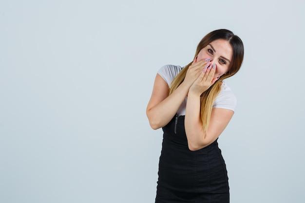 Mulher jovem cobrindo a boca com as mãos enquanto sorri
