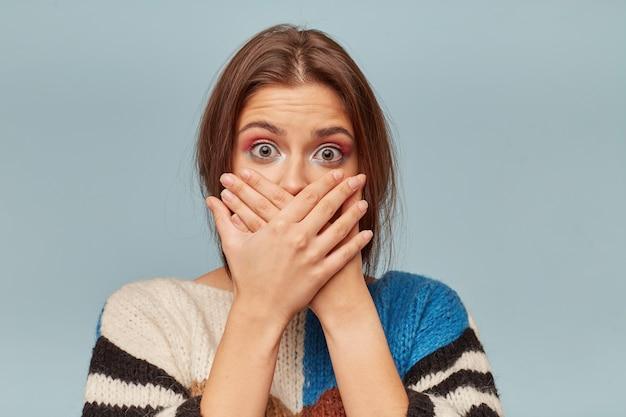 Mulher jovem cobrindo a boca com as mãos