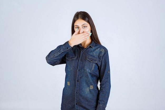 Mulher jovem cobrindo a boca e mantendo silêncio