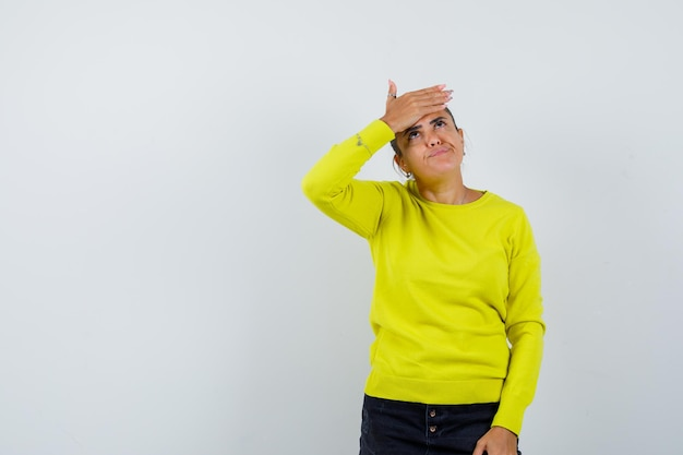 Mulher jovem cobrindo a testa, olhando para cima, com um suéter amarelo e calça preta e parecendo pensativa