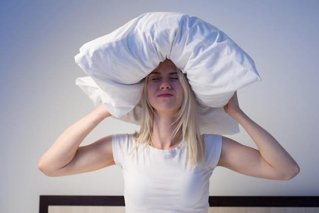 Mulher jovem cobrindo as orelhas com o travesseiro por causa do barulho.
