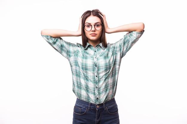 Mulher jovem cobrindo com as mãos as orelhas, sobre o branco