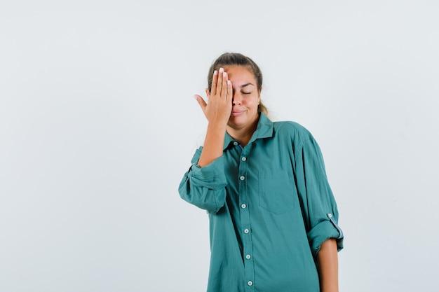 Mulher jovem cobrindo o olho direito com a mão na camisa azul e parecendo feliz