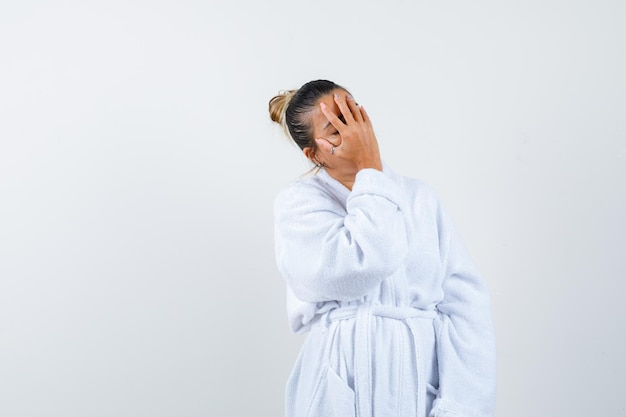 Mulher jovem cobrindo o rosto com a mão no roupão de banho e parecendo esquecida