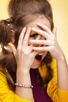 Mulher jovem cobrindo o rosto com as mãos e olhando por entre os dedos