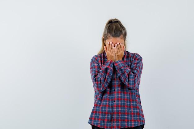 Mulher jovem cobrindo o rosto com as mãos em uma camisa xadrez e parecendo assustada