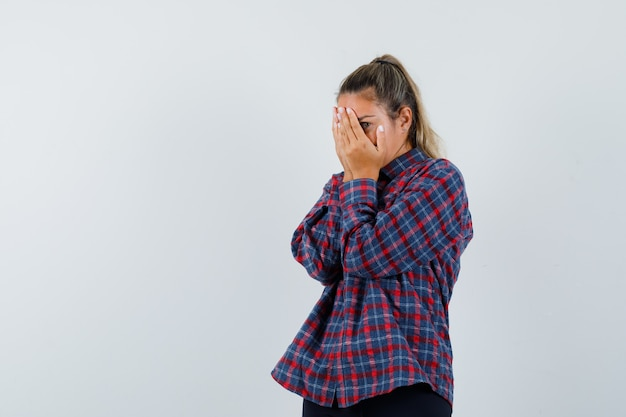 Mulher jovem cobrindo o rosto com as mãos, olhando por entre os dedos em uma camisa xadrez e parecendo assustada