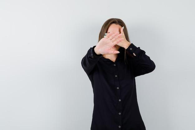 Mulher jovem cobrindo o rosto com as mãos