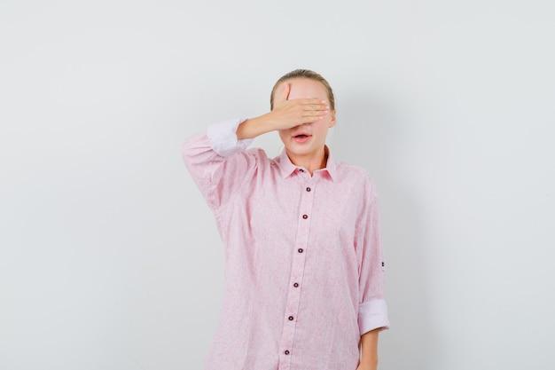 Mulher jovem cobrindo os olhos com a mão em uma camisa rosa