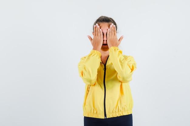 Mulher jovem cobrindo os olhos com a mão na capa de chuva amarela e parecendo assustada