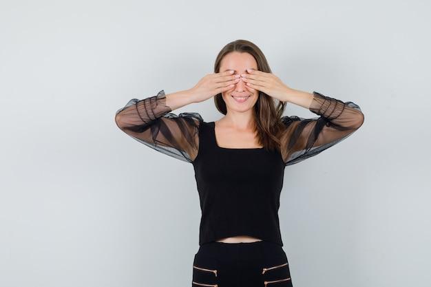 Mulher jovem cobrindo os olhos com as duas mãos em uma blusa preta e calça preta e parece feliz. vista frontal.