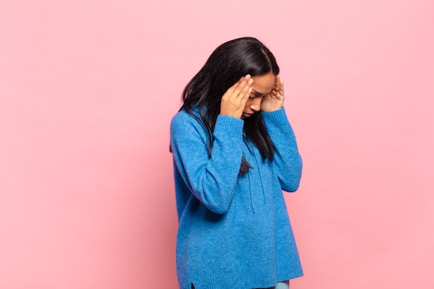 Mulher jovem cobrindo os olhos com as mãos com um olhar triste e frustrado de desespero, chorando, vista lateral