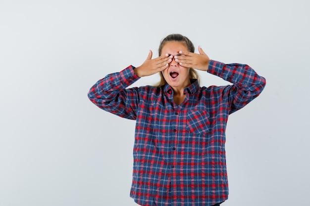 Mulher jovem cobrindo os olhos com as mãos e bocejando, com uma camisa xadrez e parecendo com sono