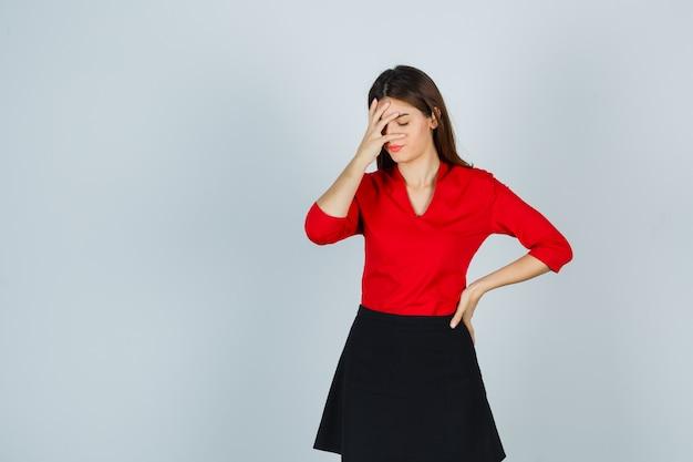 Mulher jovem cobrindo parte do rosto com a mão, segurando a mão no quadril com uma blusa vermelha