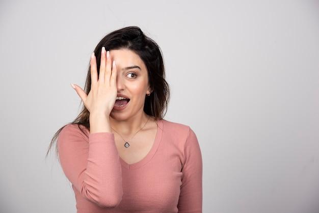 Mulher jovem cobrindo um olho com a mão e olhando para a câmera.