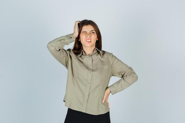 Mulher jovem coçando a cabeça enquanto franze a testa na camisa e parece esquecida