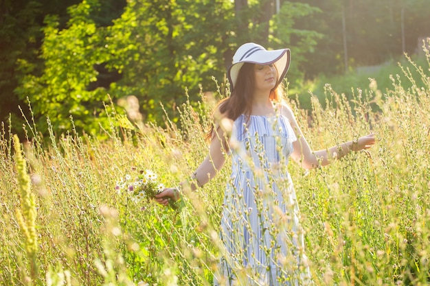 Mulher jovem colhendo flores no prado na noite de verão
