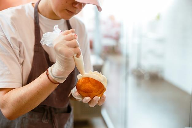 Mulher jovem coloca creme dentro de pão em padaria artesanal