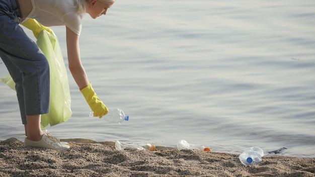 Mulher jovem coloca o lixo em um saco de lixo. uma mulher com luvas de borracha limpa garrafas de plástico vazias da margem do lago. salvação e conservação da natureza. 4k uhd