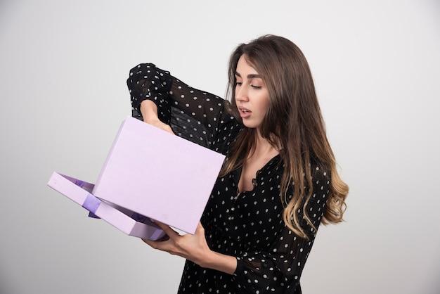 Mulher jovem colocando a mão em uma caixa de presente roxa