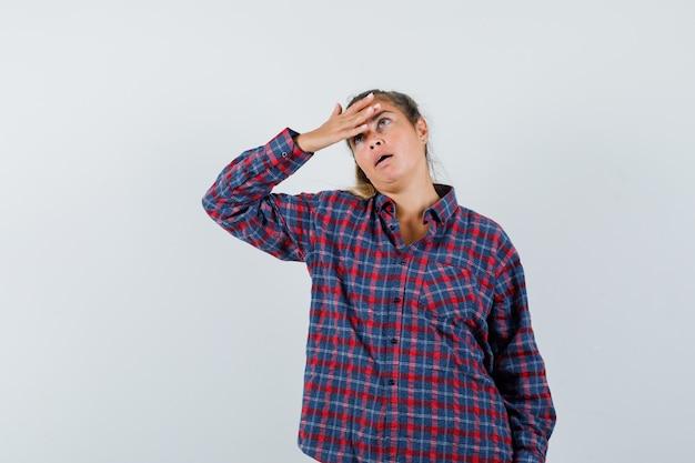Mulher jovem colocando a mão na testa com uma camisa xadrez e parecendo preocupada