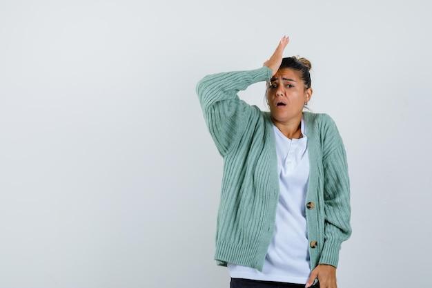 Mulher jovem colocando a mão na testa em uma camiseta branca e um casaco de lã verde menta e parecendo irritada