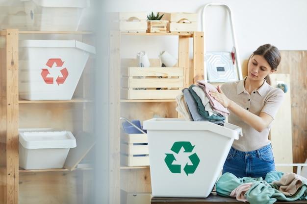 Mulher jovem colocando suas roupas velhas na lixeira de plástico ecológico e reciclando as roupas