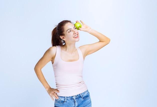 Mulher jovem colocando uma maçã verde no olho