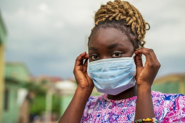 Mulher jovem colocando uma máscara protetora no rosto durante a pandemia de covid-19