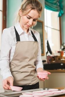 Mulher jovem, colocar, a, coloridos, papel, caixas, em, a, muffins, assando bandeja