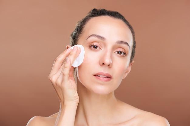 Mulher jovem com a beleza natural da pele aplicando tônico hidratante ou água micelar no rosto durante o procedimento de tratamento de beleza matinal
