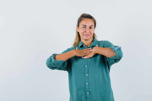 Mulher jovem, com a mão no peito, com uma blusa verde, parecendo feliz