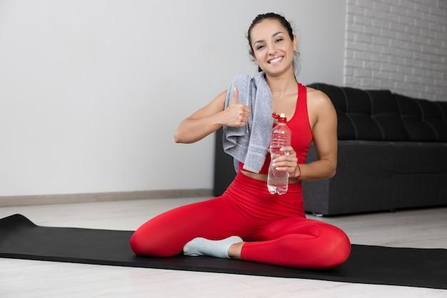 Mulher jovem com agasalho vermelho fazendo exercícios ou ioga em casa